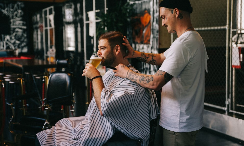 Person receiving a haircut and drinking a beer